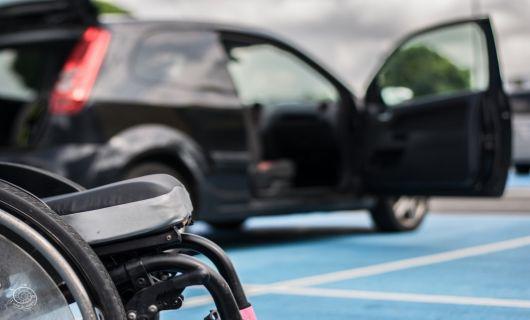 Voiture sur parking PMR avec voiturette